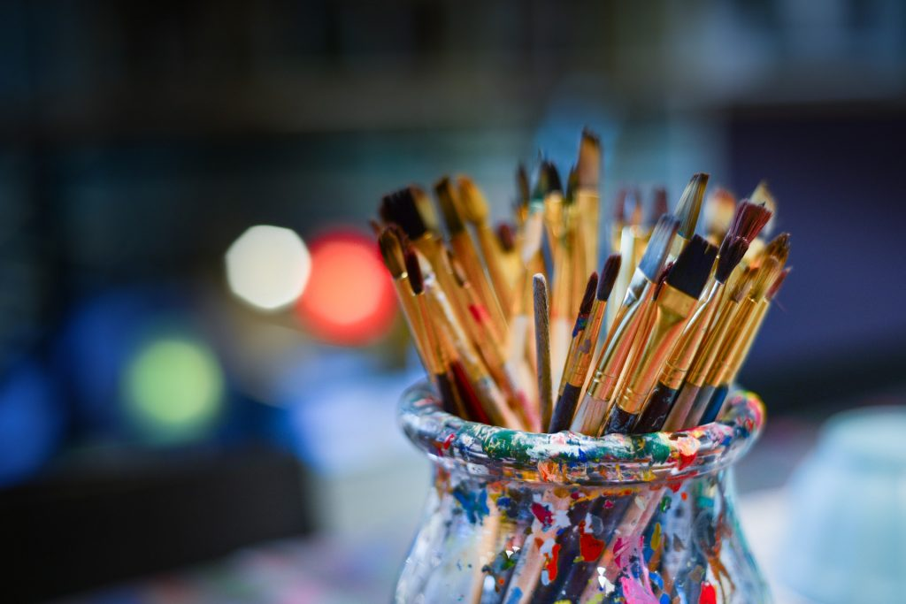 assortment of paintbrushes in a glass bottle with random paint splotches.
